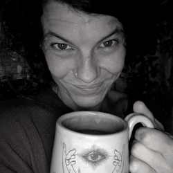 Meg, smiling and holding a cup of tea